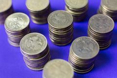 Le monete stanno sulle colonne su un fondo delle viole Fotografia Stock