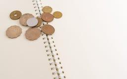 Le monete sullo spazio in bianco aprono il taccuino Immagini Stock Libere da Diritti