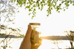 Le monete in vetro del barattolo con il fondo della natura, risparmiano i soldi per preparano in futuro Risparmio di concetto per Fotografie Stock Libere da Diritti