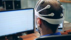Le moniteur avec l'information transmise d'un casque d'EEG a mis dessus un homme banque de vidéos