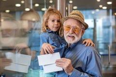 Le monsieur âgé optimiste pose avec la petite fille à l'aéroport Images libres de droits