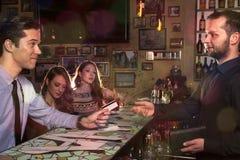 Le monsieur invite ses amis et salaire avec la carte de crédit à la Co Images stock