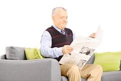 Le monsieur supérieur a assis sur un sofa moderne lisant un journal Photographie stock