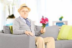 Le monsieur supérieur s'asseyant sur un divan et se tenant fleurit à la maison Image stock