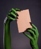 Le monstre vert remet tenir le morceau vide de carton photo stock