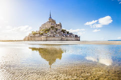 Le Mont Saint-Michel tidal island in Normandy, France. Panoramic view of famous Le Mont Saint-Michel tidal island on a sunny day with blue sky and clouds stock photo