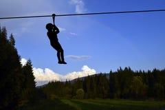 Le montagne abbelliscono con la siluetta di un bambino che gioca con un apprendista Fotografie Stock