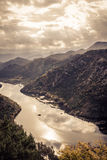 Le montagne abbelliscono nei colori tonificati arancio intorno alla curva del fiume di Rijeka Crnojevica dall'alta vista nel gior Fotografie Stock