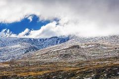 Le montagne coperte in neve sotto le nuvole lanuginose abbelliscono Fotografie Stock