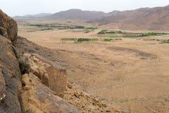 Le montagne del deserto abbelliscono con alcuni campi lontani verdi Fotografia Stock