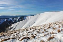 Le montagne dell'inverno abbelliscono con cielo blu nel giorno soleggiato Fotografia Stock