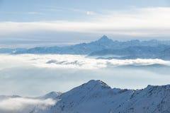 Le montagne della neve in lampadina, l'inverno luminoso del giorno soleggiato sulle alpi, alti picchi di montagna, nebbia e nuvol Fotografie Stock