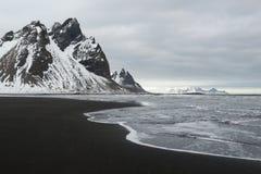 Le montagne della penisola, di Vestrahorn di Stokksnes e l'oceano nero della sabbia costeggiano la linea, Islanda fotografia stock