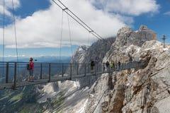 Le montagne di Dachstein dell'austriaco con le viandanti che passano uno skywalk rope Immagini Stock