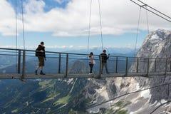 Le montagne di Dachstein dell'austriaco con le viandanti che passano uno skywalk rope Fotografia Stock