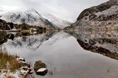Le montagne di Glyder spolverate neve che aumentano nelle nuvole hanno riflesso in Llyn Ogwen Fotografia Stock