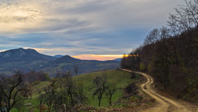 Le montagne di Homolje abbelliscono con una strada campestre della ghiaia di bobina al tramonto di un giorno soleggiato di autunno Immagine Stock