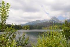Le montagne di Tatra abbelliscono il panorama con erba verde e le nuvole bianche Lago ed acqua in priorità alta Parco nazionale d Immagini Stock