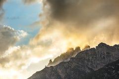 Le montagne lapidano i picchi con le nuvole arancio nell'ambito della luce del tramonto Fotografie Stock Libere da Diritti