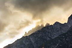 Le montagne lapidano i picchi con le nuvole arancio nell'ambito della luce del tramonto Immagini Stock Libere da Diritti