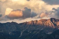 Le montagne lapidano i picchi con le nuvole arancio nell'ambito della luce del tramonto Fotografia Stock