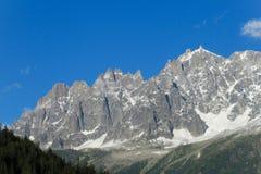 Le montagne nevicano e pendii rocciosi nelle alpi Fotografia Stock