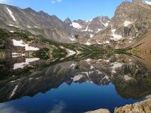 Le montagne ricoperte neve riflettono in un lago Immagine Stock