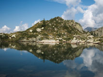 Le montagne riflettono sul piccolo lago alpino sulle alpi di Bergamo Immagine Stock