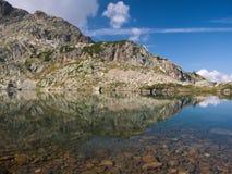 Le montagne riflettono sul piccolo lago alpino sulle alpi di Bergamo Fotografia Stock