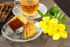 Le mooncake délicieux et le thé chaud avec un jaune fleurissent des éléments Photographie stock