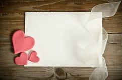 le morceau de papier se trouvant avec les coeurs et le ruban sur un dos en bois Photos libres de droits
