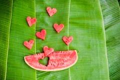 Le morceau de pastèque et de coeurs au fond de la banane part Configuration plate Images stock