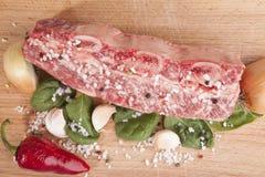 Le morceau en gros plan de boeuf marbré frais, poivre de piment, persil, oignon, ail, nervures se trouvent sur un plateau en bois Photographie stock libre de droits