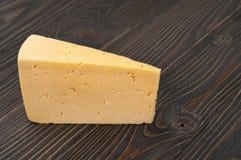 Le morceau triangulaire de fromage sur une surface en bois foncée image stock