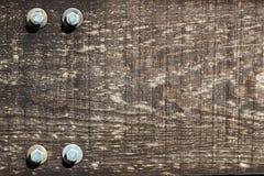 Le morceau vue de vieux bois avec quelques boulons donnent au fond une consistance rugueuse Images stock