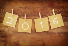 Le mot 2016 écrit sur la pince à linge a coupé des cartes devant le fond en bois Photographie stock