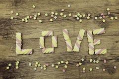 Le mot AMOUR écrit avec des guimauves Jour du ` s de Valentine et concept d'amour sur le fond en bois Images libres de droits