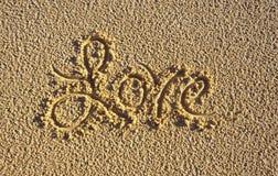 Le mot 'amour' écrit dans le sable Images stock