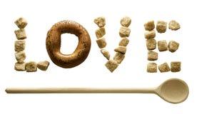 Le mot `` amour `` a fait du sucre et du bagel foncés avec une cuillère en bois horizontale sur le fond d'isolement Photographie stock libre de droits