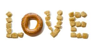 Le mot `` amour `` a fait du sucre et du bagel foncés sur un fond d'isolement Photographie stock