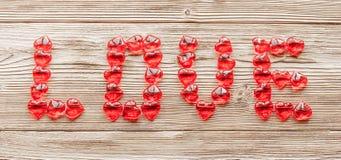 Le mot AMOUR a signalé rassemblé des coeurs rouges sur un fond de la texture en bois Image libre de droits