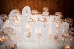 Le mot AMOUR sur le tissu blanc autour des bougies brûlantes handmade paysage Images stock