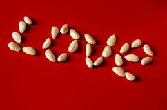 Le mot AMOUR a téléchargé des amandes sur un fond rouge Image stock