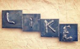 Le mot COMME fait à partir des lettres en métal Image libre de droits