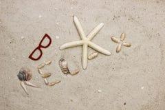 Le mot DÉTENDENT sur la plage sablonneuse avec des lunettes de soleil Photo stock