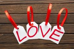 Le mot d'amour est écrit dans les étiquettes de blanc le fond en bois Photos stock