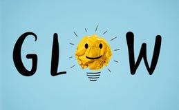 Le mot de lueur avec le papier jaune a chiffonné l'ampoule de boule photo stock