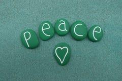 Le mot de paix avec le vert a peint des pierres de mer au-dessus du sable vert Photographie stock libre de droits