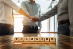Le mot de travail d'équipe sur la table en bois avec le travail d'équipe d'affaires joignent des mains à Photos stock