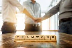 Le mot de travail d'équipe sur la table en bois avec le travail d'équipe d'affaires joignent des mains à Image stock